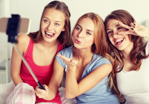 A group of friends take selfies to share on social media.